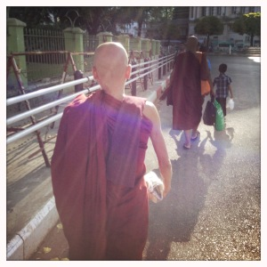 Monks walking in lanes of traffic outside Sule. www.garygeboyphotography.com